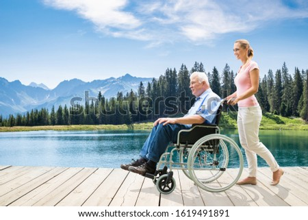 Woman Assisting Her Grandfather In Wheelchair Walking Near Lake Stock photo © AndreyPopov