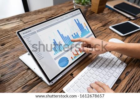 Businesswoman Analyzing Graph On Laptop Stock photo © AndreyPopov