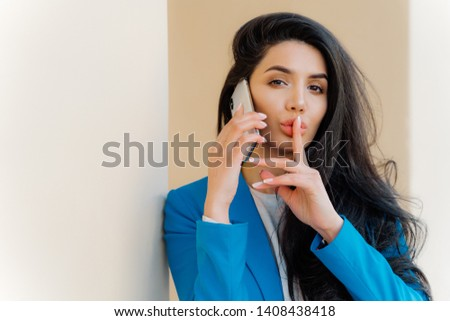 Mysterious brunette woman with makeup, talks with business party, tells secret, makes silent gesture Stock photo © vkstudio