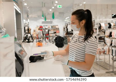 Woman in a clothing store in a medical mask because of a coronovirus. Quarantine is over, now you ca Stock photo © galitskaya
