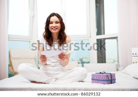 Happy woman reading a letter in her bedroom. She recieved a lett Stock photo © HASLOO