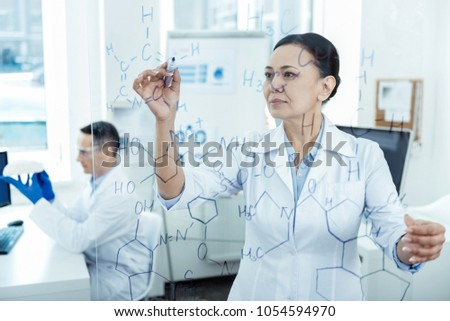 Dark-haired scientist conducting an experiment while looking at a blue flask Stock photo © wavebreak_media