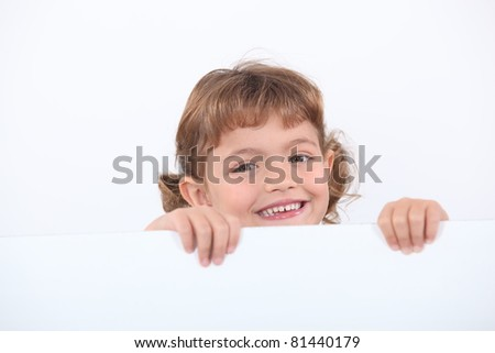 little blonde girl laughing is half hidden behind a white panel stock photo © photography33