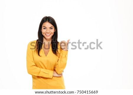 cheerful young businesswoman pointing finger away at copyspace stock photo © deandrobot
