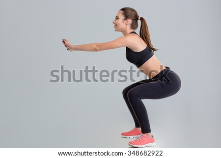 portrait of a young pretty sportswoman doing squats with dumbbells stock photo © deandrobot