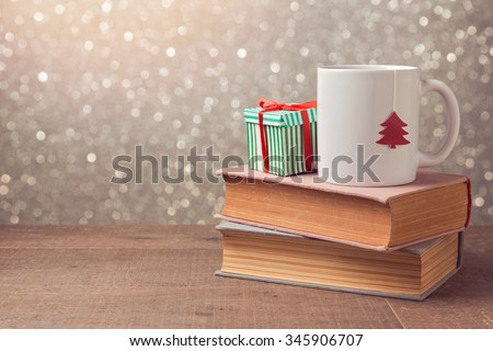 Christmas celebration with cup and gift box on books over bokeh  stock photo © TanaCh