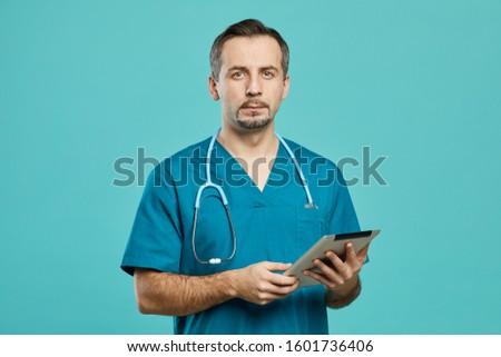 portrait of male surgeon standing with digital tablet in corridor stock photo © wavebreak_media