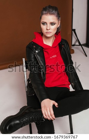 blonde woman with colorful rock outfit sitting with legs crossed Stock photo © feedough