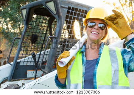 Stock photo: Female Worker Holding Technical Blueprints Near Small Bulldozer