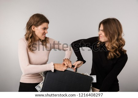 Image of two caucasian girls fighting for diplomat with dollars  Stock photo © deandrobot