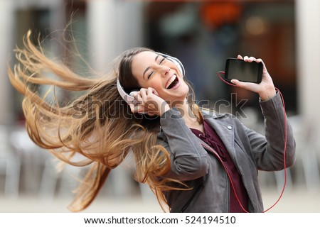 Excited woman using phone listening music with earphones isolated over red background. Stock photo © deandrobot