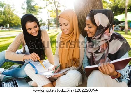 Photo of three muslim girls wearing headscarfs, sitting on blank Stock photo © deandrobot