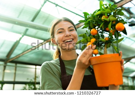 Image of pretty florist woman 20s wearing apron carrying basket  Stock photo © deandrobot