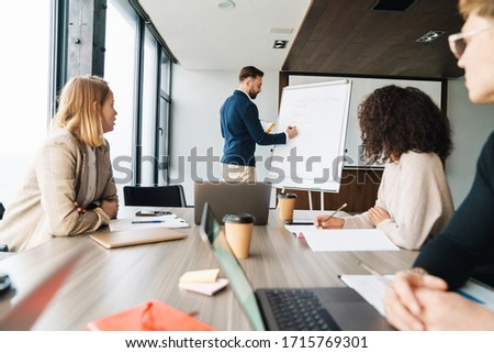 young businessman sitting and presenting a blank board to side stock photo © feedough