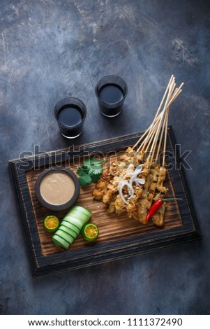 indonesian chicken satay or sate ayam served with lontong soy sauce and peanut sauce lifestyle food stock photo © galitskaya