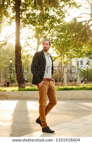 Full length image of unshaved attractive guy 30s with tied hair  Stock photo © deandrobot