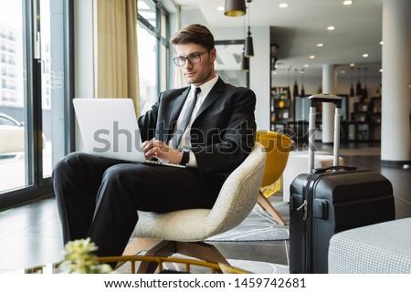 Portrait of handsome businesslike man wearing suit and earpod ba Stock photo © deandrobot