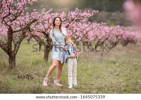 Woman and boy are standing by flowering bush of lilac. She smells flowers. Family time together. Stock photo © ElenaBatkova
