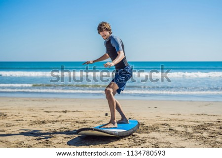 Young man surfer training before go to lineup on a sand beach. Learning to surf. Vacation concept. S Stock photo © galitskaya