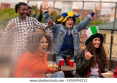 Three happy girls and guy cheering for their team during broadcast outdoors Stock photo © pressmaster