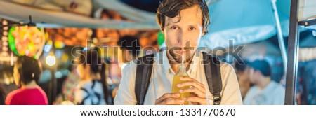 Férfi iszik cukornád dzsúz ázsiai piac Stock fotó © galitskaya