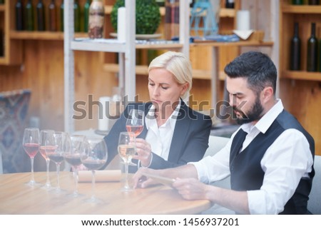 Two co-working sommeliers sitting by table with group of wine samples Stock photo © pressmaster