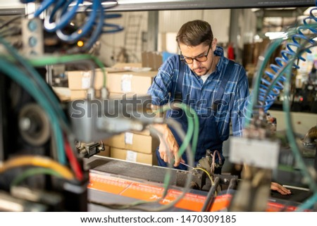 Young repairman or technician serving broken industrial machine Stock photo © pressmaster