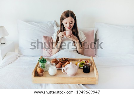 young woman eating breakfast on a tray with fruit buns avocado sandwiches smoothie bowl by the po stock photo © galitskaya
