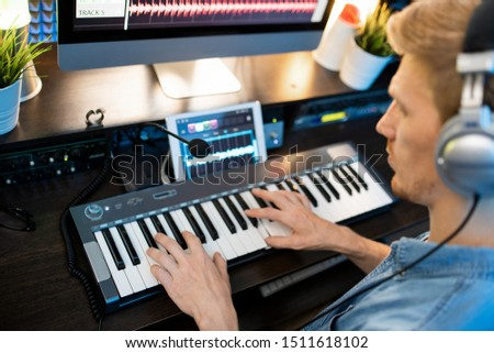 Hands of young man on piano keyboard during work over new music recording Stock photo © pressmaster