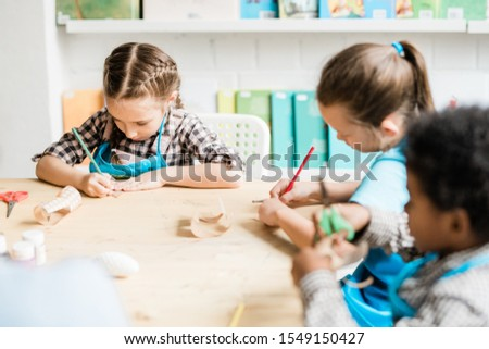 Cute intercultural schoolkids sitting by table and drawing halloween symbols Stock photo © pressmaster