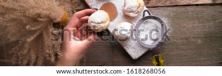 Top view of woman hand decorating with icing sugar some profiteroles. Rustic style. Stock photo © Illia