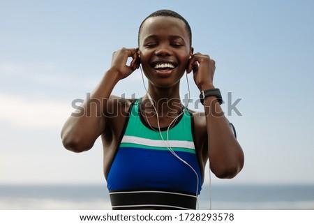 Woman listening to music while having break from running sport in winter Stock photo © Kzenon