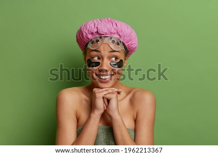 Pretty young cheerful female with under-eye patches keeping hand by her chin Stock photo © pressmaster