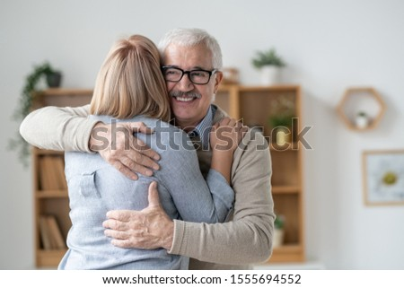 Happy and affectionate senior man giving hug to his blonde young daughter Stock photo © pressmaster