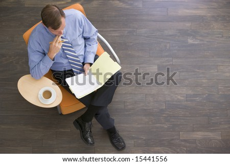 High angle view of middle-aged businessman with coffee cup using mobile phone in modern office build Stock photo © wavebreak_media
