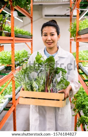 Happy young Asian agronomist carrying packed fresh organic food in wooden box Stock photo © pressmaster