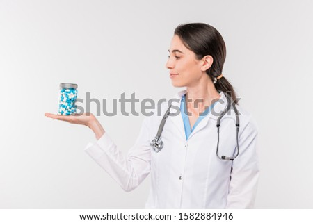 Pretty young female clinician in whitecoat holding jar and blisters with pills Stock photo © pressmaster