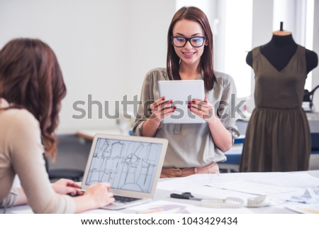 Young creative fashion designers discussing sketches while gathered in studio Stock photo © pressmaster