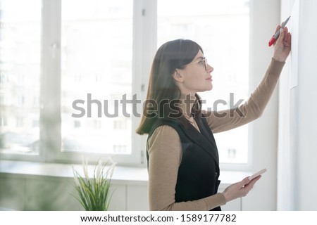 Elegant coach with smartphone writing down on whiteboard during presentation Stock photo © pressmaster