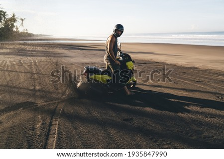 Horizontal outdoor view of active male motorcyclist rides bike, wears trendy sunglasses and black ja Stock photo © vkstudio