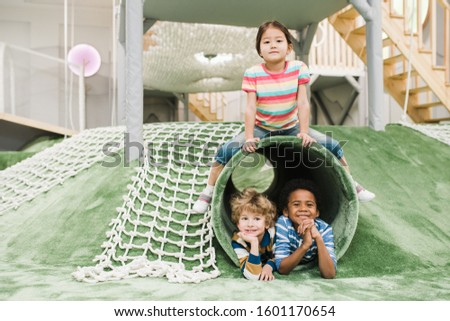 Cheerful and friendly intercultural little kids having fun together on play area Stock photo © pressmaster