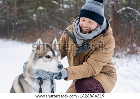 Young smiling man in winterwear cuddling purebred siberian husky dog Stock photo © pressmaster