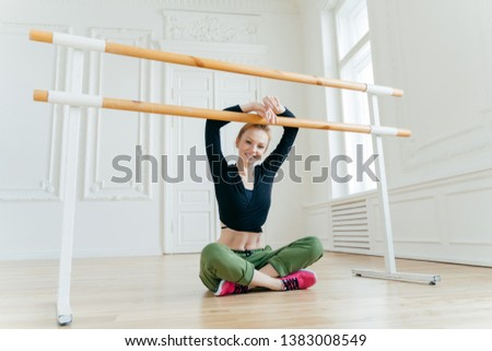 Pleased young female dancer sits in lotus pose, keeps hands on ballet barre, has rest after choreogr Stock photo © vkstudio
