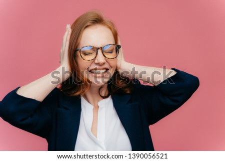 Frustrated young businesswoman has headache, ignores loud noise, covers ears with hands, clenches te Stock photo © vkstudio