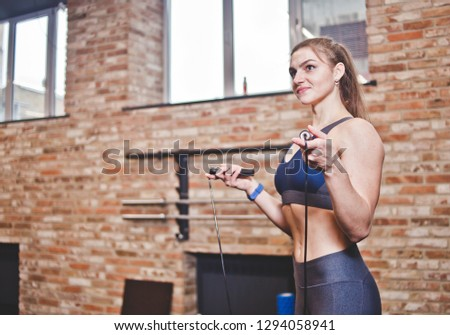 Photo of young slim woman holding jump rope and looking at camera Stock photo © deandrobot