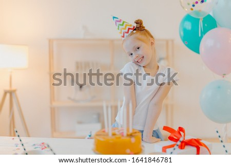 Little ginger girl wears party hat and white tshirt, stands near festive table with cake, blows cand Stock photo © vkstudio