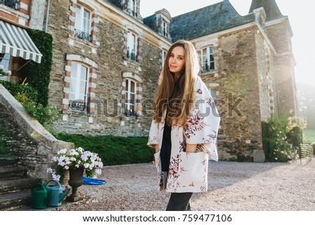 Portrait of atrrative woman wears white loose cape, stands outdoor against ancient builduing, has ex Stock photo © vkstudio