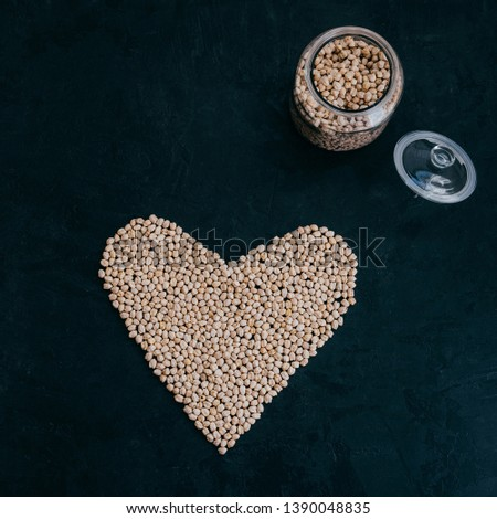Dry clean chickpeas in glass jar. Heart made of organic uncooked garbanzo. Black background. Plant b Stock photo © vkstudio