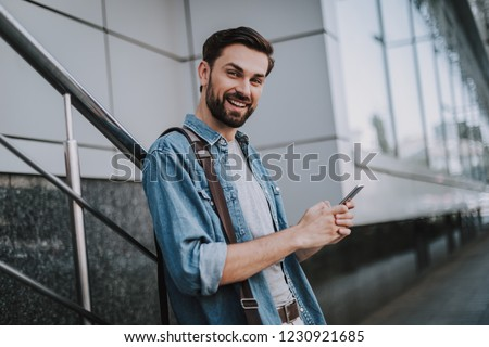 Image of bearded man holding smartphone and standing by building Stock photo © deandrobot
