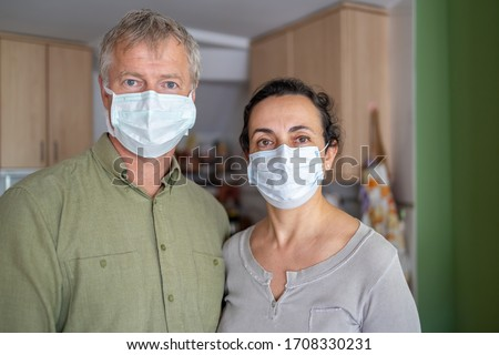 Two middle aged person with protective mask at home due to coronavirus quarantine Stock photo © digoarpi
